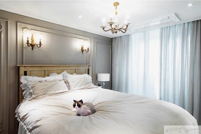 벽등과 샹들리에로 임팩트를 더해 부티크 호텔처럼 꾸민 침실. 리넨 커튼과 침구가 내추럴한 멋을 더한다.