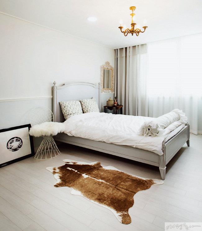게스트룸은 클래식한 민트 그레이 침대와 거울, 수납장, 골드 샹들리에, 애니멀 패턴 러그가 어우러져 로맨틱하다.