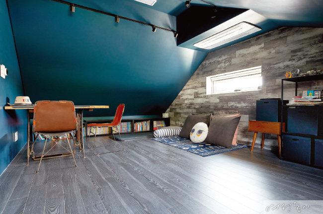 박공지붕 아래 틈새 공간은 중학생 아들이 자유롭게 휴식을 취할 수 있는 다락방으로 꾸몄다. 짙은 네이비 컬러를 포인트로 사용했으며, 한쪽 벽에 낮은 책장을 놓아 짜임새 있게 공간을 활용했다.