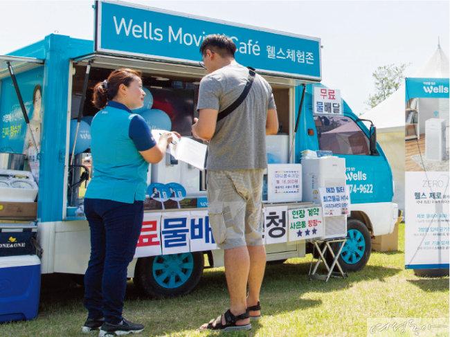 움직이는 웰스 체험관 '웰스 무빙 카페'에서 웰스 매니저가 제품에 대해 설명하고 있다.