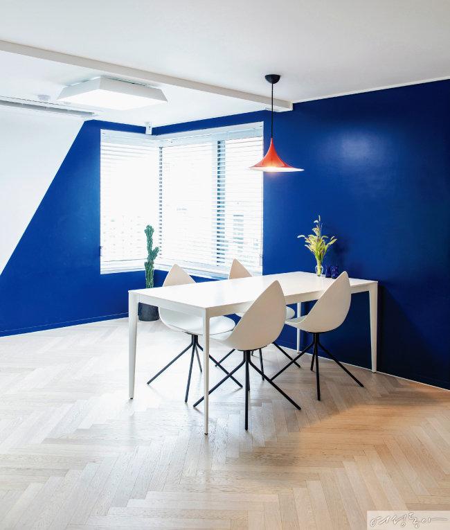 블루 컬러 페인트를 사선으로 칠해 유니크하게 연출한 1층 거실. 테이블과 의자는 화이트로 통일하고 레드 조명을 달아 포인트를 주었다.