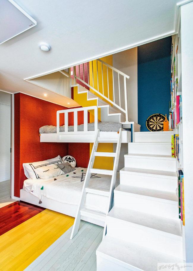 벽과 바닥을 4등분해 레드, 옐로, 그레이, 블루 컬러로 꾸민 아이 방이 동화 같다. 다락방으로 올라가는 계단 벽에 책장을 짜 넣은 아이디어도 눈여겨볼 것.