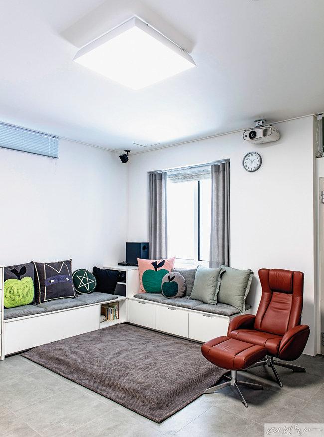 핸드프린팅 쿠션을 레어어드해 감각적인 풍경을 완성한 홈시어터룸.