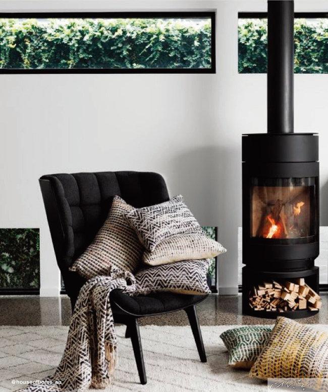 노르딕 패턴 니트 쿠션과 블랭킷이 따뜻한 감성을 자아내는 공간. 화목난로가 인테리어에 힘을 더한다.