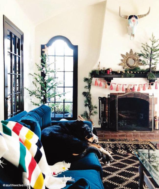 벽난로를 트리로 꾸민 크리스마스 데코. 독특한 디자인의 헌팅 트로피와 러그가 이국적이다.