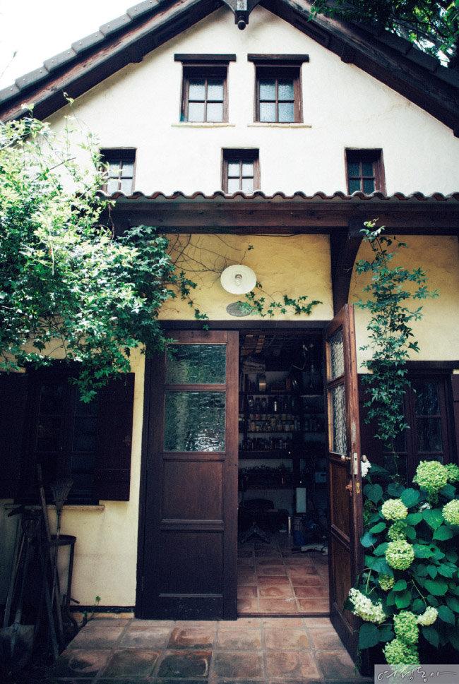 아틀리에로 사용하는 작은 집은 삼각 지붕, 작은 창들, 규조토 벽으로 이뤄져 있다. 입구 바닥부터 집 안까지 이어지는 테라코타 타일과 앤티크 초콜릿색 현관문은 아름다움 그 자체. 기초공사와 축조는 목수에게 의뢰하고 현관문과 창문 등은 직접 만들어 설치한 결과물이다.
