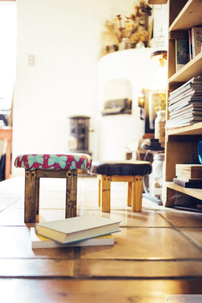 둥근 쟁반을 활용해 만든 스툴. 리빙 숍에서 구입한 원목 쟁반에 다리를 붙인 뒤 천과 가죽을 덧씌워 레트로 스타일 스툴을 완성했다.