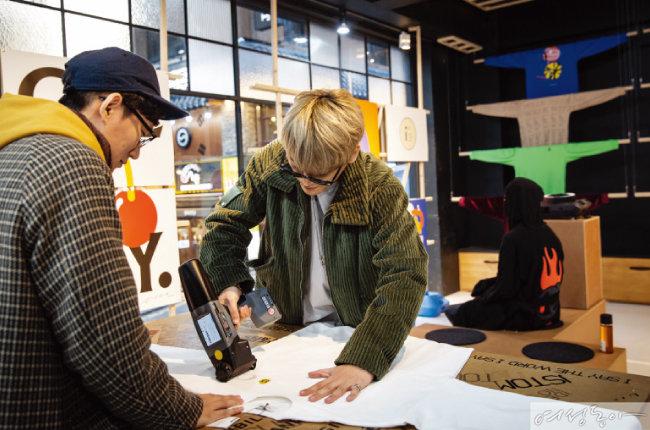 핸드젯 프린터를 이용해 티셔츠 커스터마이징 중인 아티스트 이덕형과 커스텀멜로우 프린츠 외관.