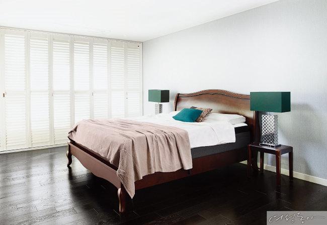 침대 양옆에 그린 컬러 스탠드를 세팅해 유니크하게 연출한 침실. 창가에는 루버셔터 우드 블라인드를 설치해 휴양지의 호텔 같은 느낌을 더했다.
