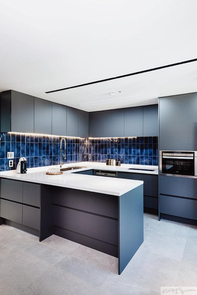 주방은 상하부 싱크대 모두 그레이 컬러로 맞추고, 블루 컬러 타일을 길게 붙여 모던한 느낌을 더했다. 싱크대는 꾸밈by조희선에서 제작한 것으로 수납공간이 넉넉해 살림살이를 깔끔히 정리할 수 있다.