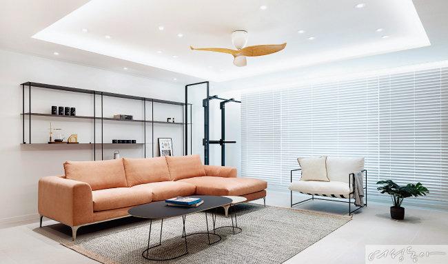 거실 한쪽에 모듈형 선반 가구를 맞춤 제작해 배치했다. 화이트와 블랙, 라이트 그레이 등 무채색 금속으로 만든 가구는 거실에 임팩트를 더한다. 베란다 확장 공간에 미니 중문을 설치해 공간을 구별한 아이디어가 돋보인다. 소파 우디크.