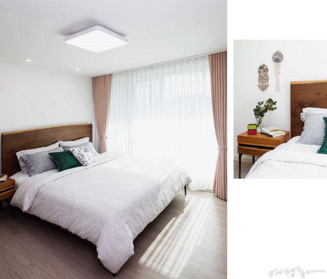 부부 침실은 원목 헤드가 임팩트를 더하는 침대와 협탁, 리넨 침구, 마크라메 벽 장식으로 내추럴하게 꾸몄다. 창가에는 화이트와 베이지 핑크 컬러 커튼을 2중으로 달았다. 침대와 협탁은 인아트. 침구와 마크라메 벽 소품은 위스홈, 커튼은 한올 C&D.