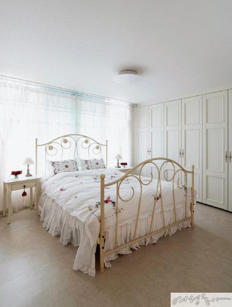 화이트 프레임 침대와 붙박이장으로 온통 하얗게 꾸민 침실은 아기자기한 꽃수가 놓인 베딩으로 포인트를 주었다.