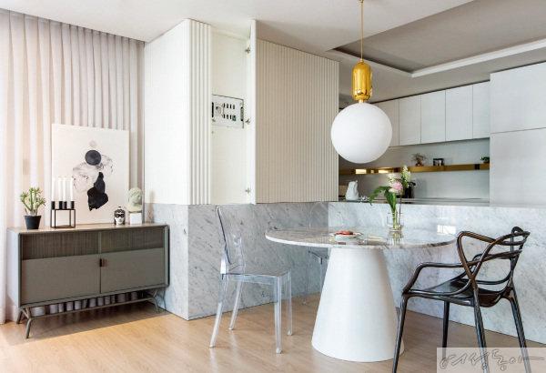 입체감이 살아 있는 월 데코와 대리석을 활용한 카페 같은 주방. 주방과 거실이 마주 보는  오픈형 다이닝 구조다.