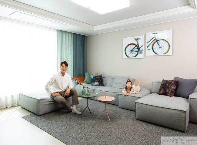 은은한 그린 컬러가 안정감을 주는 거실에서 아나운서 김환과 딸 다니가 휴식을 취하고 있다. 소파는 에싸, 카펫은 투유바이조희선, 액자는 그림닷컴.