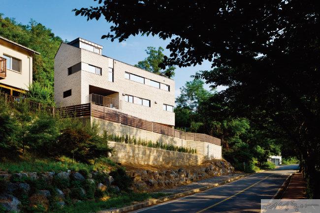동백동 숲 집의 외관. 경사지였던 땅에 벽돌과 나무 등 자연 소재를 활용해 'ㅅ'자 지붕이 돋보이는 독립된 집을 지었다.