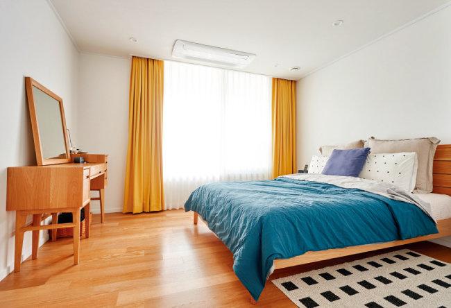 우드 톤과 잘 어울리는 원색 패브릭과 침구류, 러그 등을 매치해 부부만의 개성과 취향을 오롯이 담은 침실.