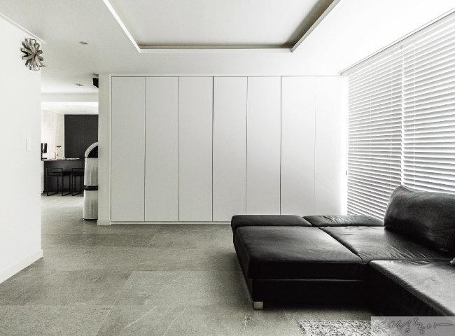 거실 한쪽 벽면 가득 설치한 화이트 컬러 시스템 수납장. 손잡이까지 없앤 미니멀한 디자인이라 마치 흰 벽처럼 보여 공간이 항상 깔끔하다.