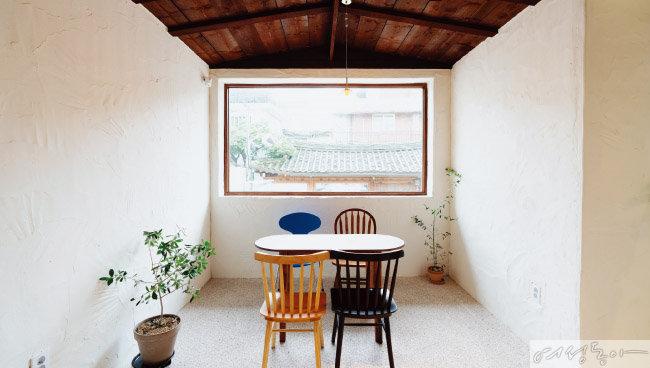슬로우 포레스트의 포토존으로 유명한 창가 자리. 커다란 창으로  한옥 지붕이 보여 멋스럽다.