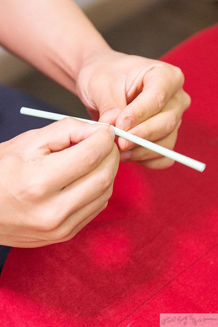 빨대 마술 비법의 포인트. 빨대를 반으로 접은 후 접힌 부분을 집게손가락으로 잡아 반대쪽으로 다시 구부린다.