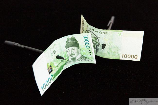 펜이 지폐를 관통한 것으로 보이지만 사실 펜은 자석을 이용한 마술도구다. 지폐는 안전하다.