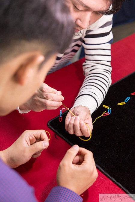 클립마술을 위한 장치를 만드는 과정. 장치의 고무줄을 팔꿈치까지 잡아 당겨 장착한 후 옷으로 가린다.