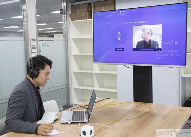 AI와 영상 면접을 시행하고 있는 기자. 컴퓨터 모니터에 면접자의 얼굴과 질문과 제한 시간이 떠 있다.