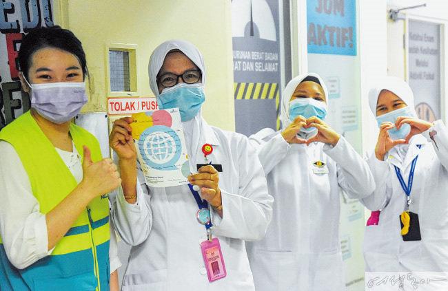말레이시아 셀랑고르주 곰박 지역 병원 의료진이 ASEZ WAO 회원들이 전해준 편지를 들고 환하게 웃고 있다. ASEZ WAO는 이곳에 간식과 손편지 1백 키트를 전달했다.