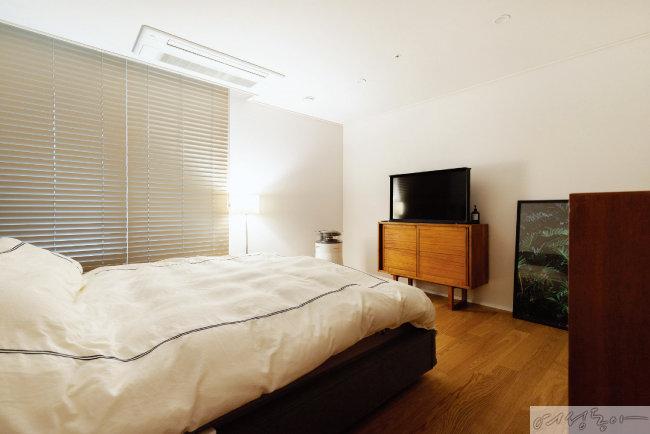 오로지 편안한 수면과 휴식을 위해 완성한 침실은 따뜻한 조도를 위해 메인 조명을 쓰지 않고 플로어 스탠드와 펜던트 조명만을 두었다.