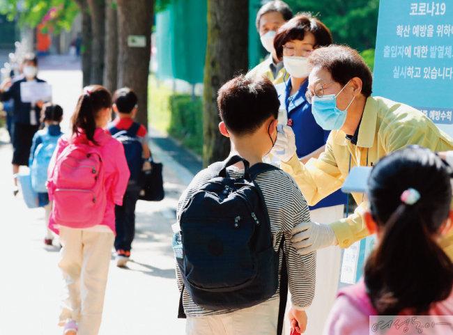 지난해 5월 조희연 교육감이 대면 등교가 시작된 서울 송파구의 한 초등학교에서 발열 체크를 돕는 모습.