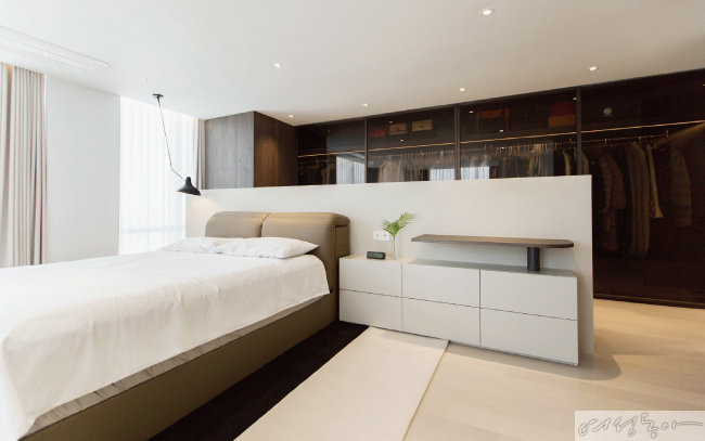 두 개의 방을 하나로 터서 안방을 만들었다.  낮은 가벽은 침대 헤드로 활용되는 동시에 안방과 드레스 룸을 분리해주는 역할을 한다.