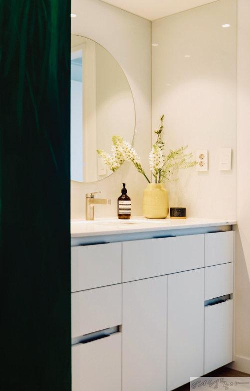 세면실에는 거실 조명을 두고, 물이 튀어도 무방한 소재로 벽을 마감했다. 벽에 거울의 조명이 반사되어 화사한 느낌을 준다.