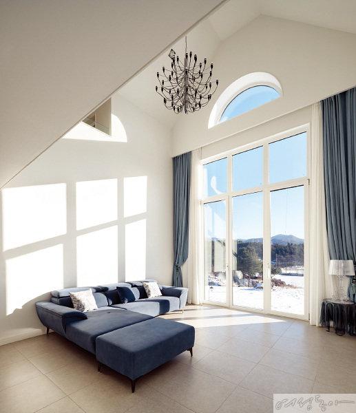 스카이블루 색상의 소파는 거실의 포인트. 창을 통해 따스하게 내리쬐는 햇살과 어우러져 아늑함을 느낄 수 있는 공간이다.