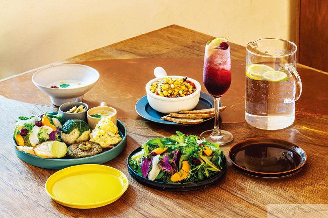 예약제 식당에서 맛볼 수 있는 제철 메뉴. 델리 숍의 모든 음식을 선보이는 샘플러 플레이트인 델리밀 정식, 완두감자수프, 여름 채소 라타투이, 오미자베리 에이드, 여름 샐러드(노란 플레이트를 기준으로 시계 방향).
