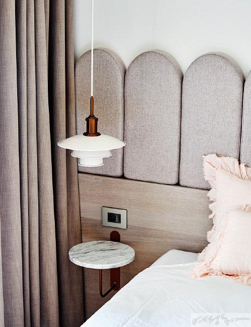 침대 헤드보드는 벽에 부착해 불필요하게 낭비되는 공간을 없앴다. 통일감을 더하기 위해 커튼과 헤드보드는 동일한 컬러를 선택했다. 크지 않은 펜던트 조명과 대리석 선반의 조화가 세련된 모습이다.