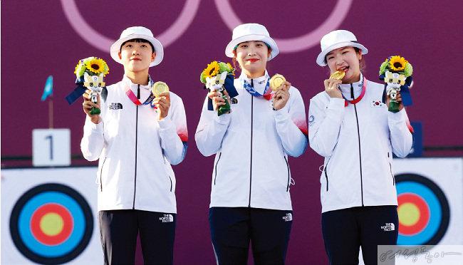 도쿄 올림픽 양궁 여자단체전에서 금메달을 획득한 안산, 장민희, 강채영(왼쪽부터) 선수가 시상대에 올라 금메달과 트로피를 들어 보이고 있다.